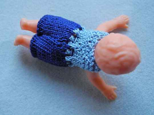 Plastic popje, buikligging, blauw en lichtblauw pakje - Plastic doll laying on its belly,blue and pale blue suit