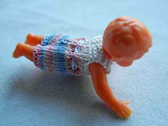 Plastic popje, buikligging,blauw-roze pakje - Plastic doll laying on its belly, pink and blue suit