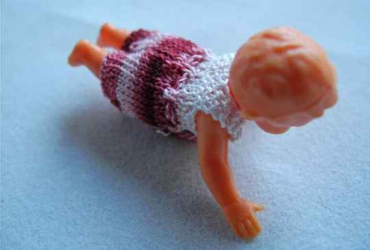 Plastic popje, buikligging, roze-bordeau pakje - Plastic doll laying on its belly,pink-burgundy  suit